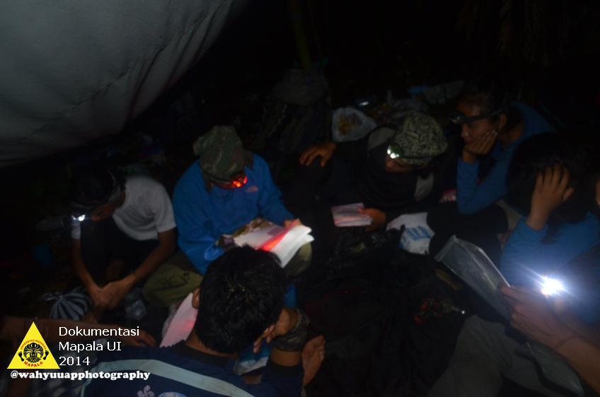Tim melakukan evaluasi malam di kemah setiap hari setelah menempuh perjalanan di hutan.